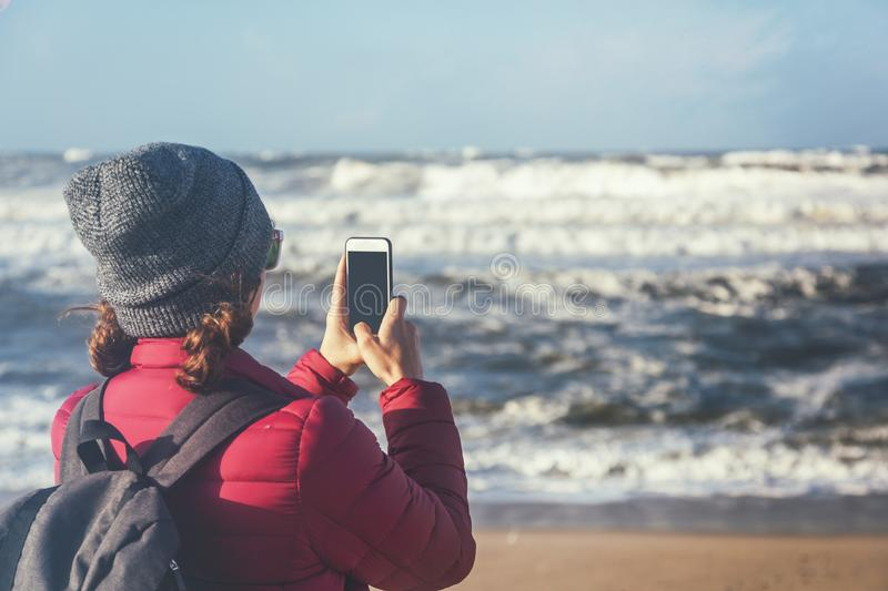 Young beautiful traveler girl with a backpack taking off the ocean and waves on a smartphone, winter, Atlantic ocean, Portugal stock photography