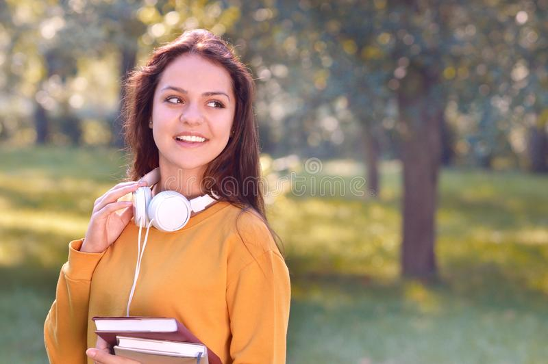 Young beautiful and trendy student girl hold books and look aside royalty free stock photography