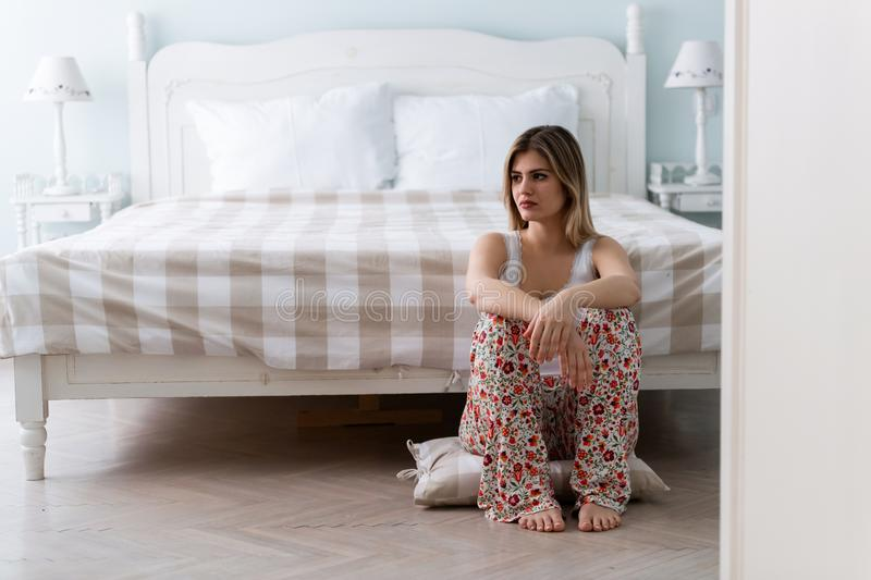 Young beautiful unhappy woman sitting in bedroom royalty free stock photo