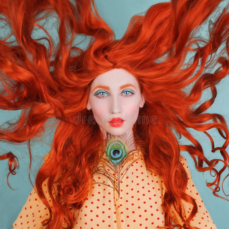 Young beautiful unusual red-haired girl with very long curly hair on a blue background. Fairytale model in a yellow dress with an unusual hairdo with a peacock stock image