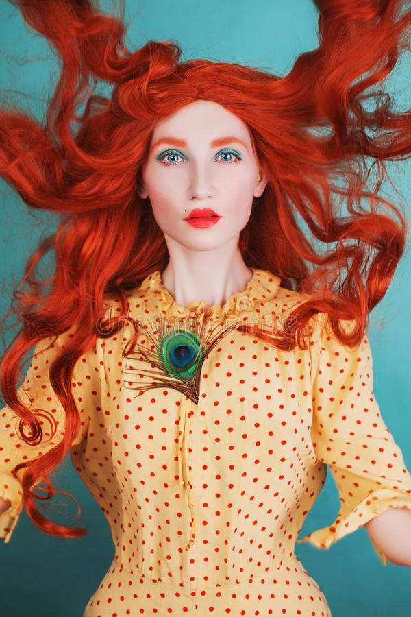 Young beautiful unusual redhead girl with very long curly hair on a blue background. Fairytale model in a yellow dress with an. Unusual hairdo with a peacock stock photos
