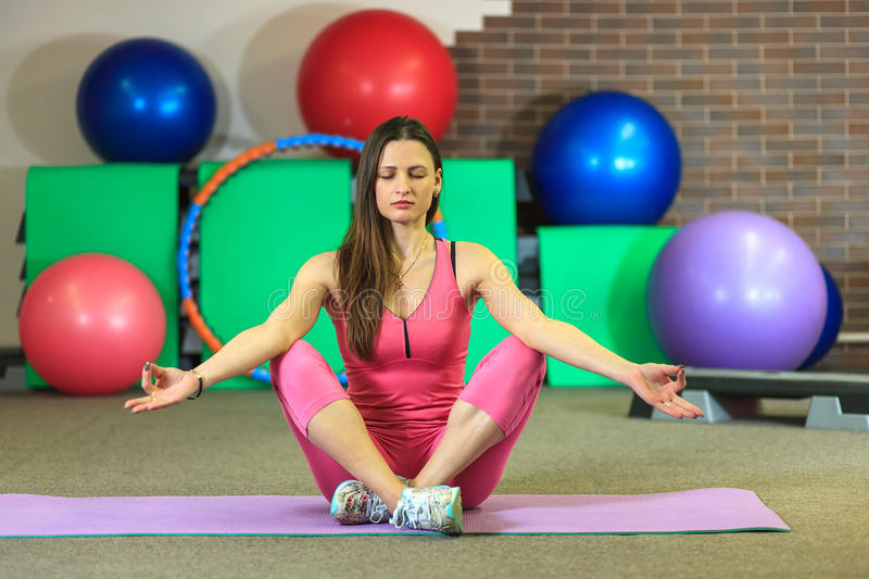 Young beautiful white girl in a pink sports suit meditates on the yoga class at the fitness center. Interior of fitness club for background stock images