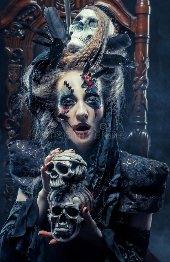 Young beautiful witch sits on a chair. Bright make up, skull, smoke- halloween theme. stock photo