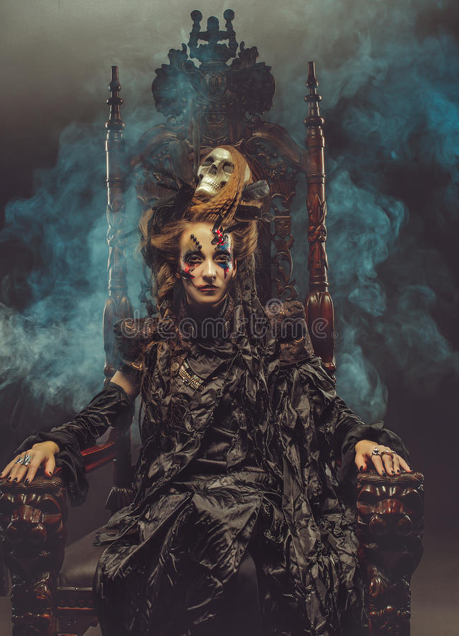Young beautiful witch sits on a chair. Bright make up, skull, smoke- halloween theme. Young witch sits on a chair. Bright make up, skull, smoke- halloween theme stock photos
