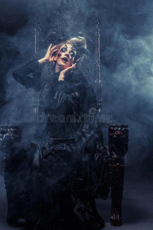 Young beautiful witch sits on a chair. Bright make up, skull, smoke- halloween theme. Young witch sits on a chair. Bright make up, skull, smoke- halloween theme royalty free stock photography
