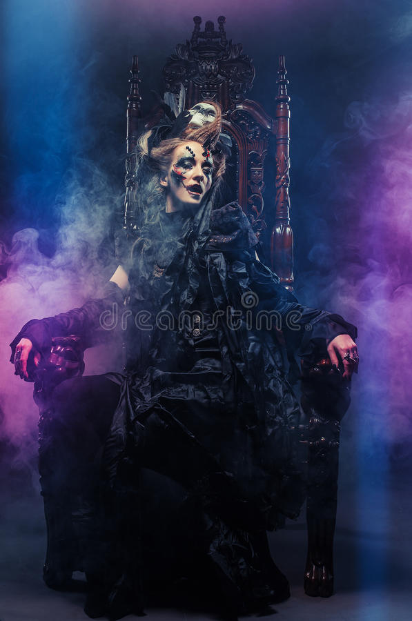 Young beautiful witch sits on a chair. Bright make up, skull, smoke- halloween theme. Young witch sits on a chair. Bright make up, skull, smoke- halloween theme stock photo