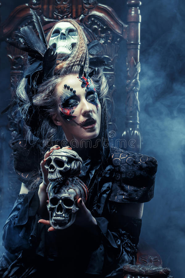 Young beautiful witch sits on a chair. Bright make up, skull, smoke- halloween theme. royalty free stock photo