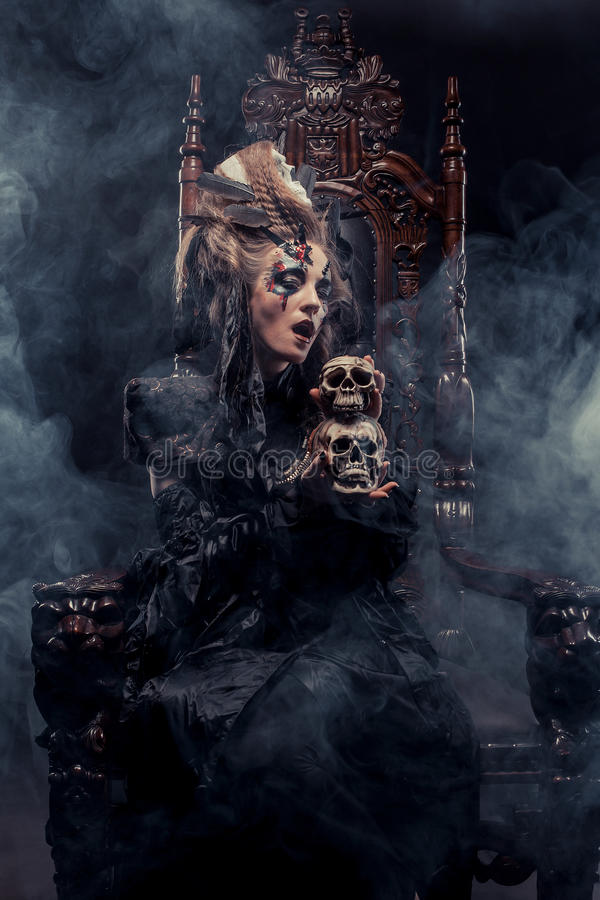 Young beautiful witch sits on a chair. Bright make up, skull, smoke- halloween theme. royalty free stock images