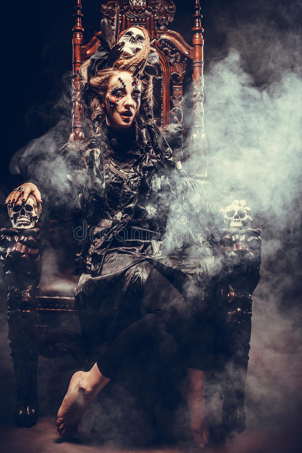 Young beautiful witch sits on a chair. Bright make up, skull, smoke- halloween theme. Young witch sits on a chair. Bright make up, skull, smoke- halloween theme royalty free stock photos