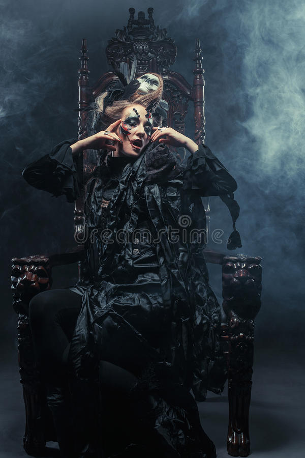Young beautiful witch sits on a chair. Bright make up, skull, smoke- halloween theme. royalty free stock image