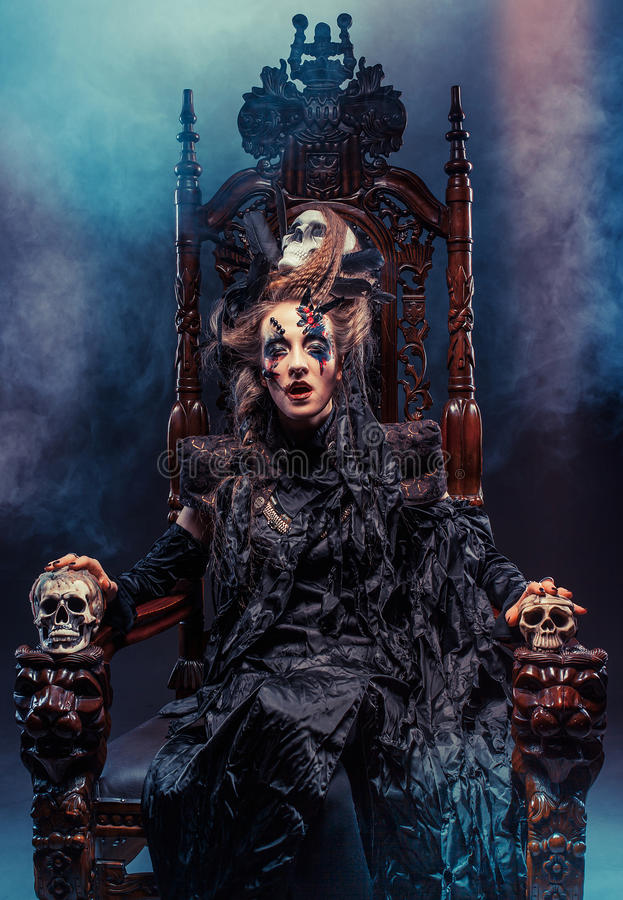 Young beautiful witch sits on a chair. Bright make up, skull, smoke- halloween theme. stock images