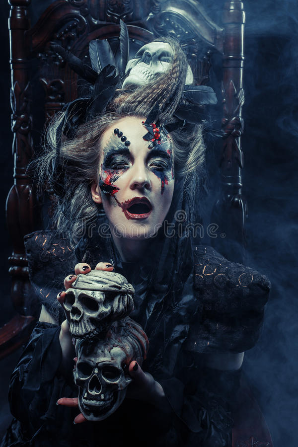 Young beautiful witch sits on a chair. Bright make up, skull, smoke- halloween theme. royalty free stock photos