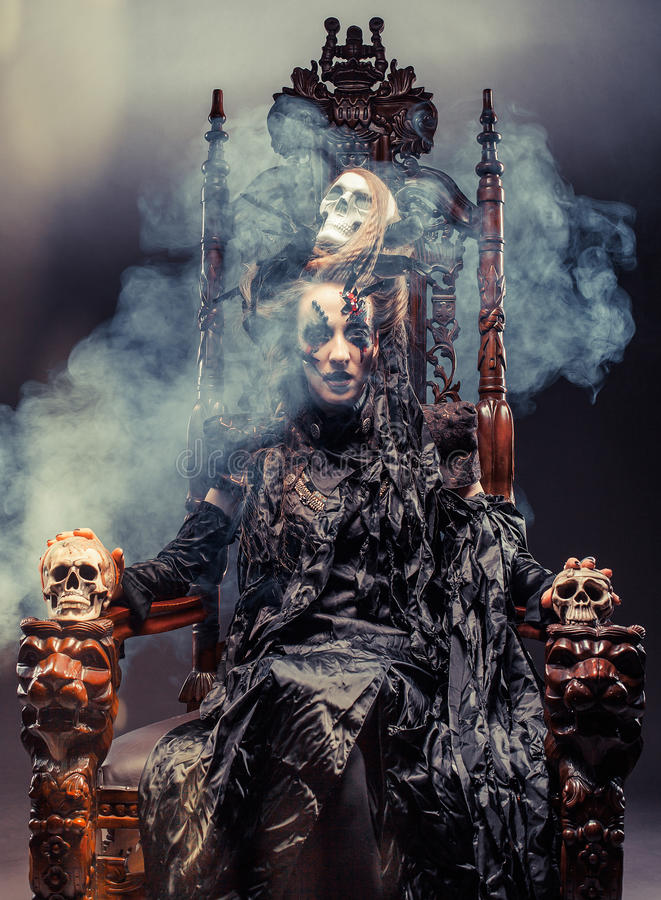 Young beautiful witch sits on a chair. Bright make up, skull, smoke- halloween theme. stock photography