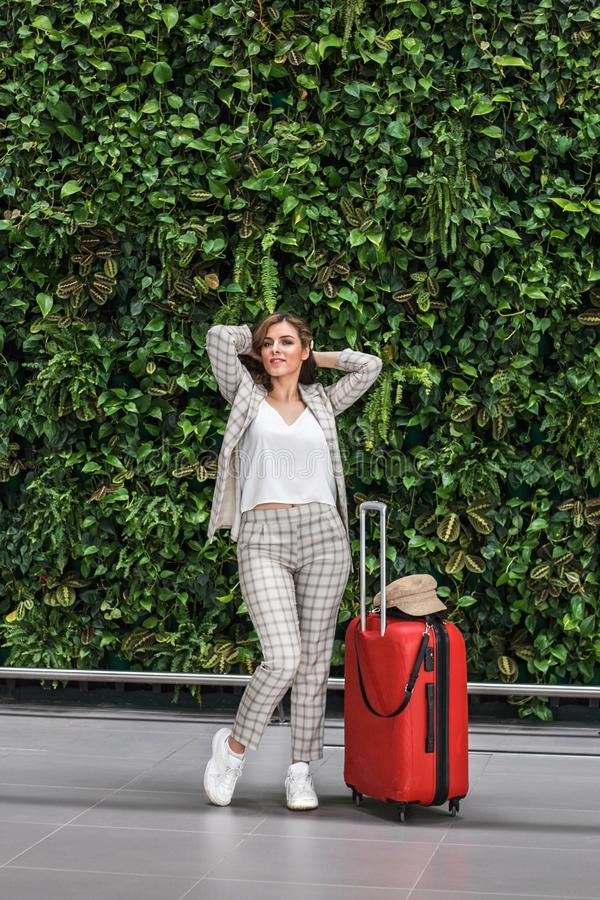 Young beautiful woman in Airport against green wall. royalty free stock images