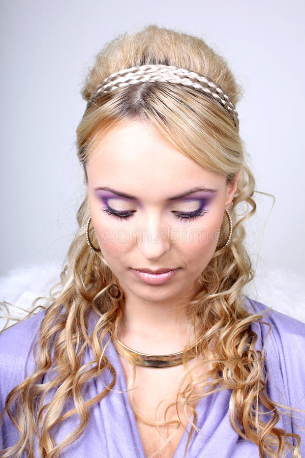 Young beautiful woman with angel wings. Young blonde in violet with angel wings stock images