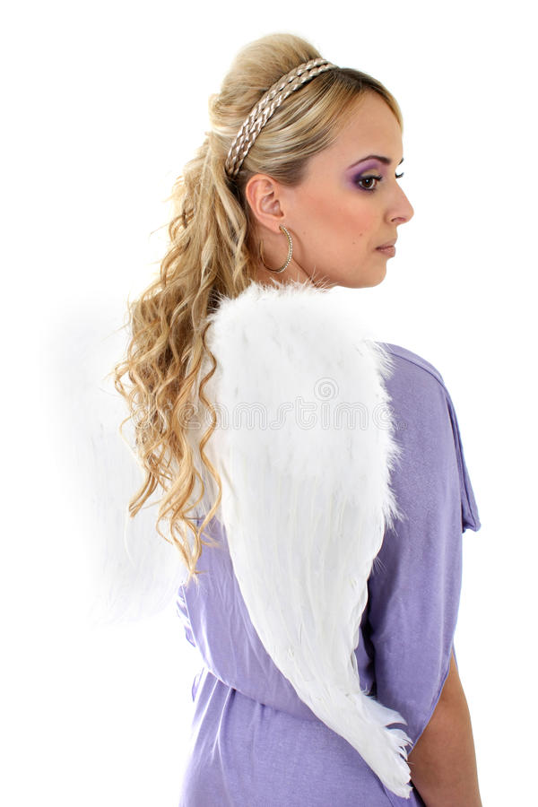 Young beautiful woman with angel wings. Young blonde in violet with curly hair and angel wings royalty free stock images