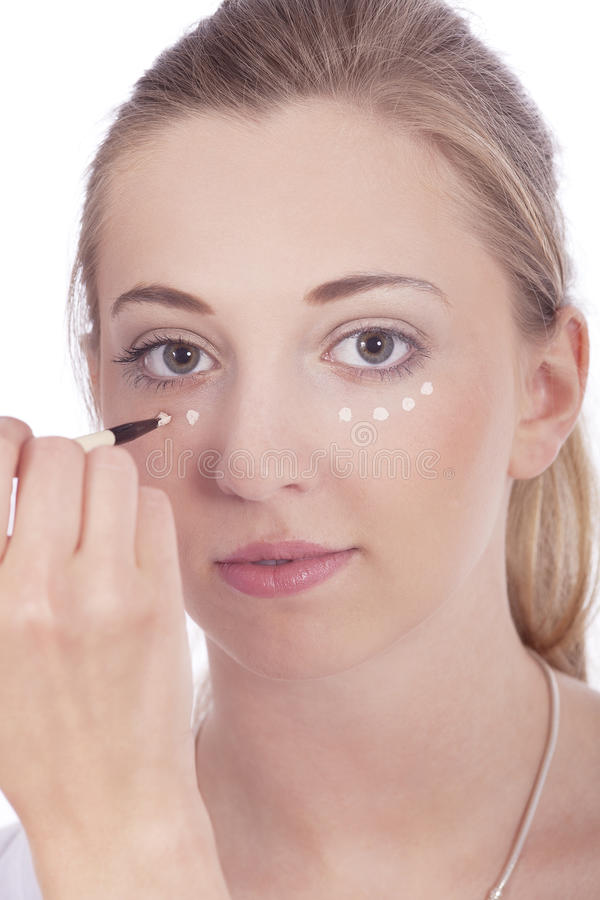 Young beautiful woman applying concealer on face. Isolated stock photography