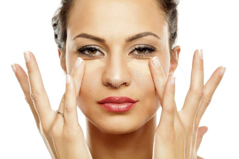 Women applying concealer. Young beautiful woman applying concealer under her eyes with her fingers stock image