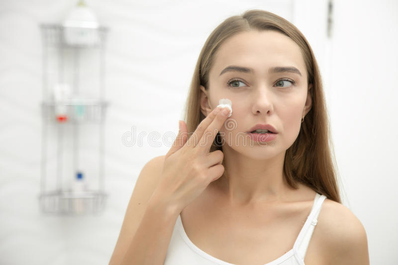 Young beautiful woman applying cream to face in the bathroom. Young beautiful woman applying cream to her face and looking worried at the mirror at home bathroom stock photography