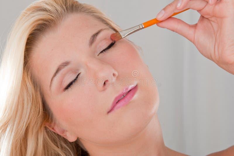 Young beautiful woman applying eye make-up stock photos