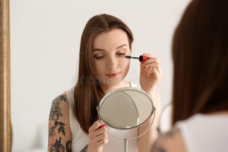 Young beautiful woman applying makeup near mirror indoors. Morning routine stock photos