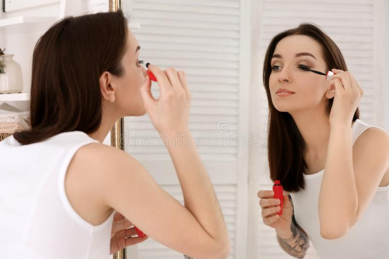 Young beautiful woman applying makeup near mirror indoors. Morning routine royalty free stock photo