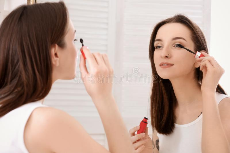 Young beautiful woman applying makeup near mirror indoors. Morning routine stock photography