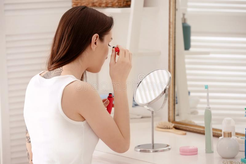 Young beautiful woman applying makeup near mirror indoors. Morning routine royalty free stock photos