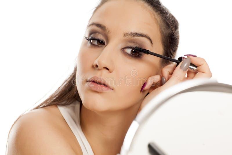 Woman applying mascara royalty free stock photography