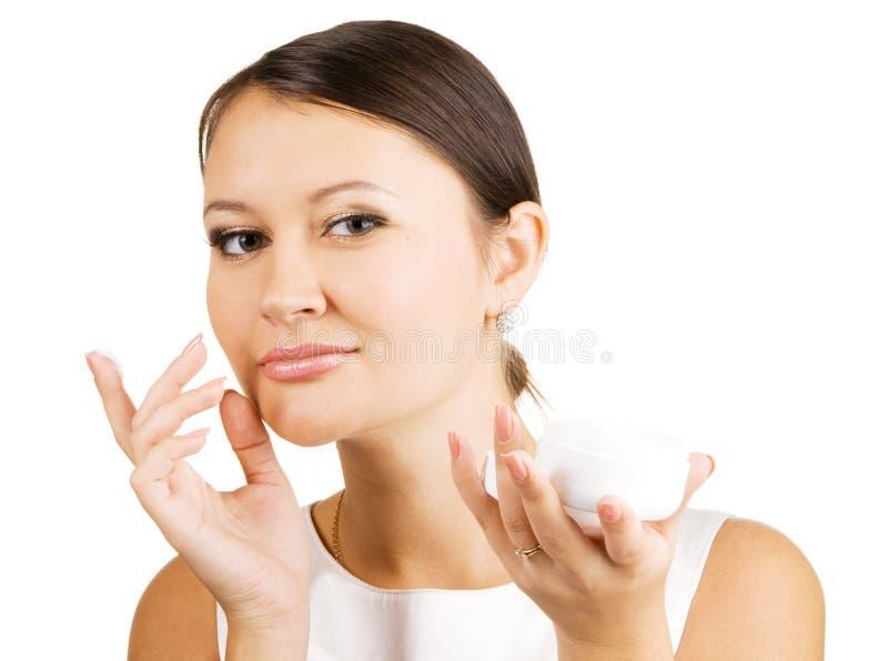 Young beautiful woman applying skin cream royalty free stock image