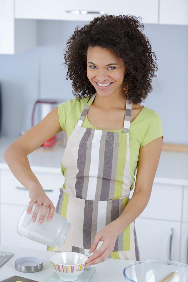 Young beautiful woman in apron making cake stock photo