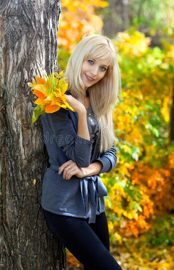 Young beautiful woman in autumn park stock photo