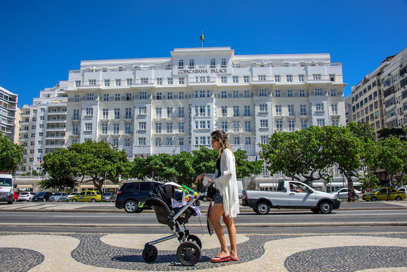 Young beautiful woman with baby carriage on the background of Copacabana Palace in Rio de Janeiro, Brazil royalty free stock image