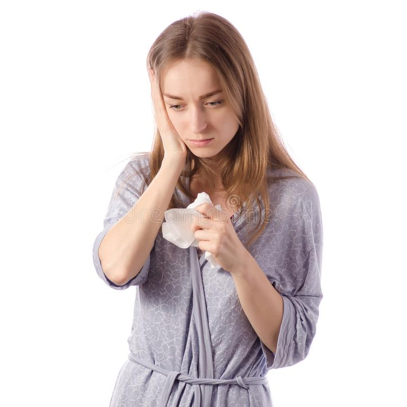 Young beautiful woman in a bathrobe has a headache cold flu napkin royalty free stock images