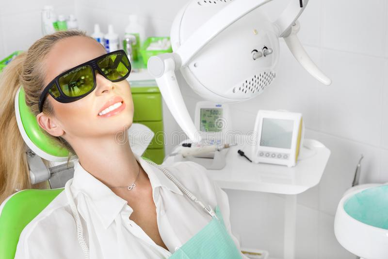 Young beautiful woman with beautiful white teeth sitting on a dental chair. The dentist cures her teeth stock photos