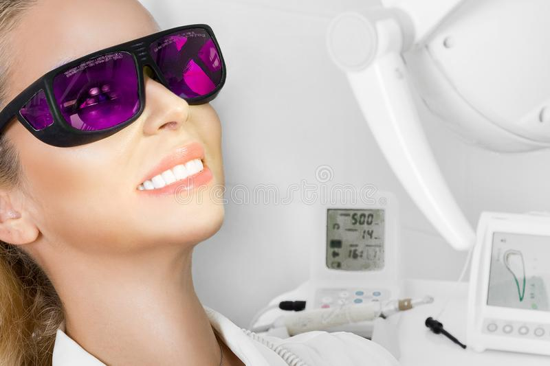 Young beautiful woman with beautiful white teeth sitting on a dental chair. The dentist cures her teeth stock photo