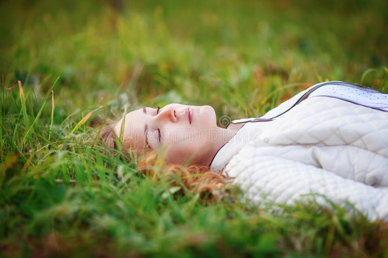 Young beautiful woman. Beauty girl lying on grass, closed eyes royalty free stock photo