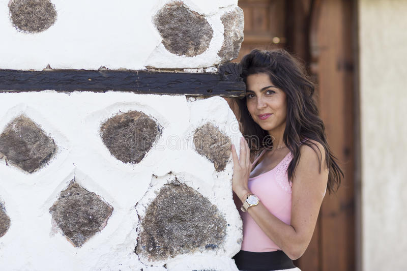 Young beautiful woman behind an old stone wall, outdoor shot. Brunette beautiful woman behind a white stone wall, outdoor shot stock image