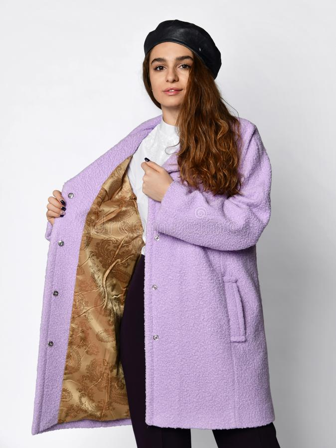 Young beautiful woman in beret demonstrates lining inside of a new medium length fashion casual pink winter jacket coat stock photography