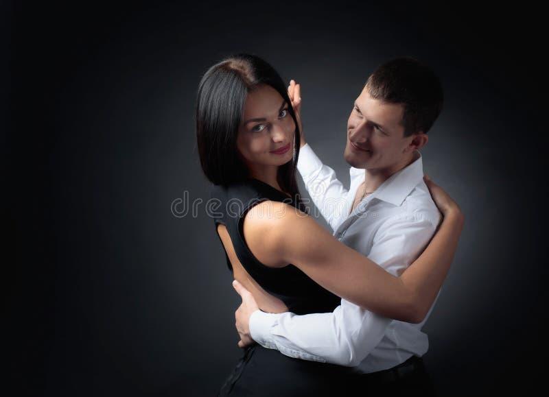 Young beautiful woman in black dress and man in white shirt dancing tango. royalty free stock photos