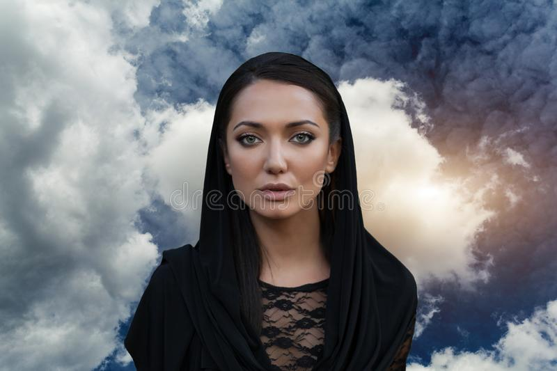 Young beautiful woman with a black hair and in the black dress with the sky backgtound royalty free stock image