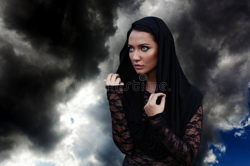 Young beautiful woman with the black hair and in the black hood and black transparent blouse at the sky background royalty free stock images