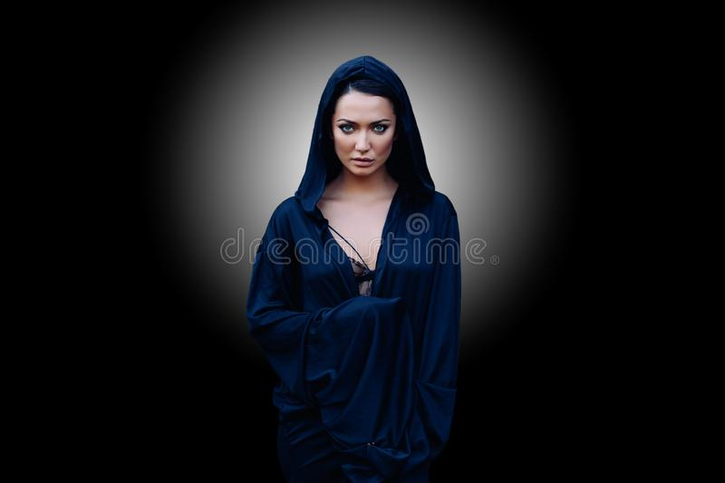 Young beautiful woman with a black hair and in the dark blue cloak with hood at the black background royalty free stock image