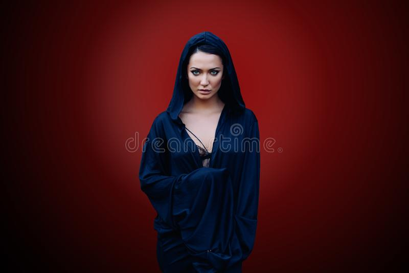 Young beautiful woman with a black hair and in the dark blue cloak with hood at the red background stock photos