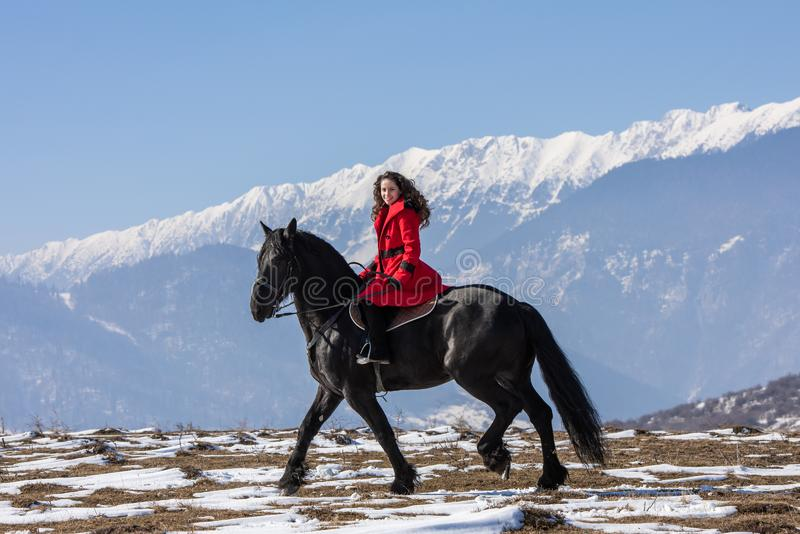 Young beautiful woman on black horse in riding in Transylvania mountains stock images