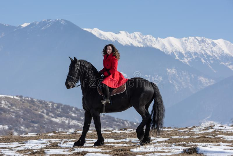 Young beautiful woman on black horse in riding in Transylvania mountains royalty free stock photo