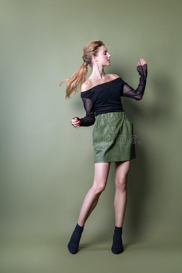 Young beautiful woman in a black jacket and green skirt posing in the Studio. Attractive female model in stylish casual clothes on royalty free stock images