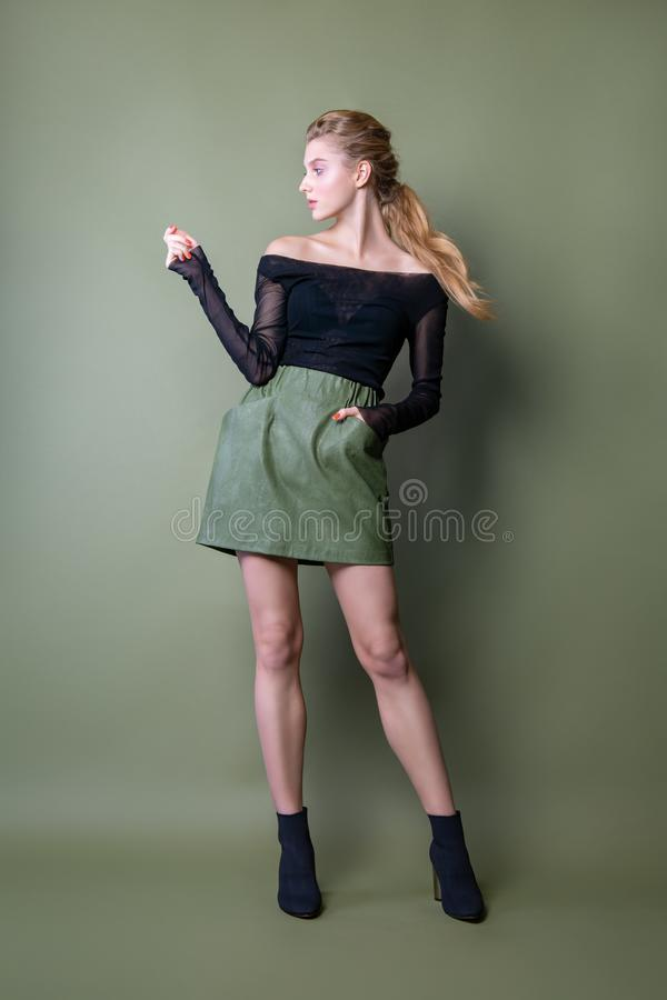 Young beautiful woman in a black jacket and green skirt posing in the Studio. Attractive female model in stylish casual clothes on stock images