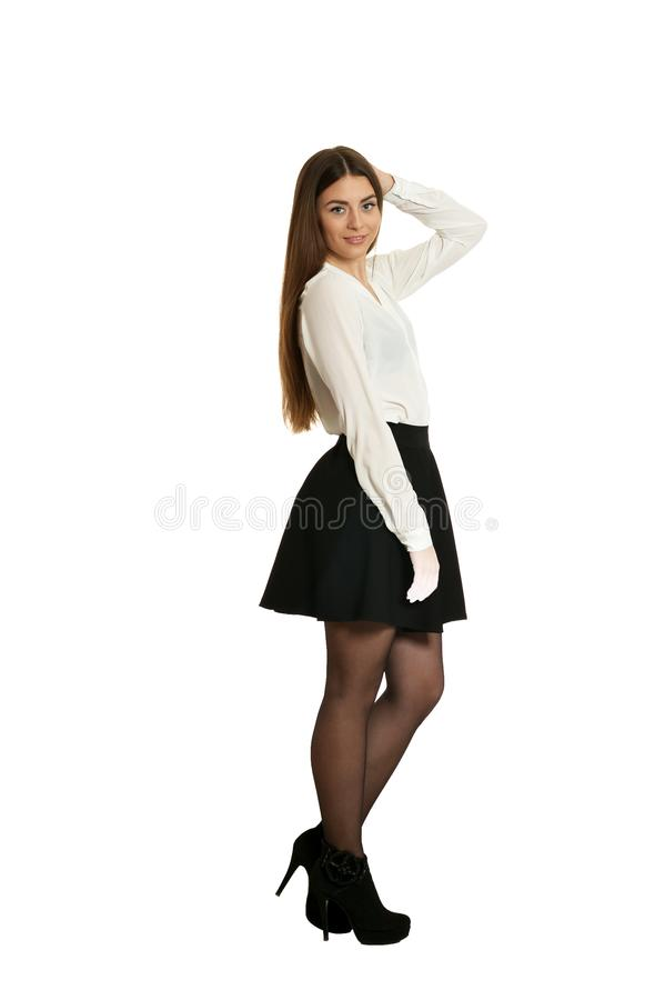 Young beautiful woman in black skirt and heels standing full length on white background. Young beautiful woman in black skirt and heels standing full length royalty free stock images