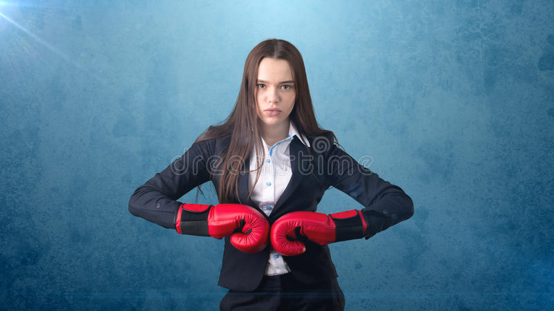 Young beautiful woman in black suit and white shirt standing in combat pose with red boxing gloves. Business concept. Young business woman dress in black suit royalty free stock photos
